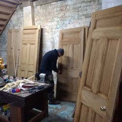 image of doors in our workshop being stripped off their paint