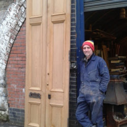 image of staff member with a recently stripped door